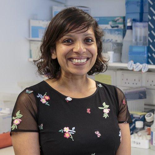 Professor Kurian standing in her lab, smiling