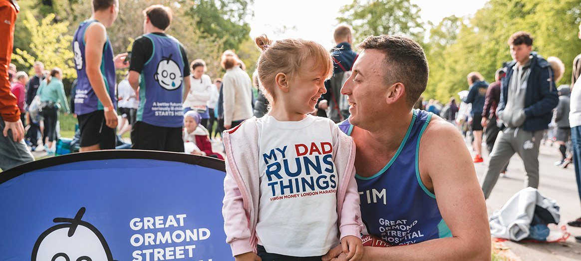 A father, about to take part in the London Marathon, hugs his smiling daughter.