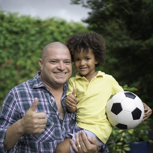 Man and son smiling at the camera giving a thumbs up
