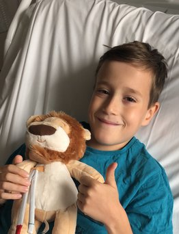 boy smiling in hospital bed and giving a thumbs up