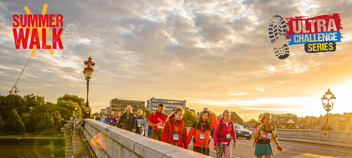 Group of people walking across a bridge in the sunshine