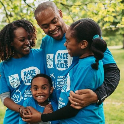 GOSH Patient Noah and his family together outside, wearing Race for the Kids t-shirts