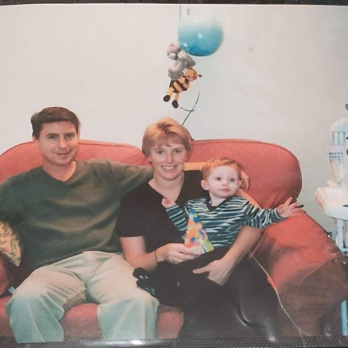 Baby Rhys sits next to his parents on a sofa on his birthday