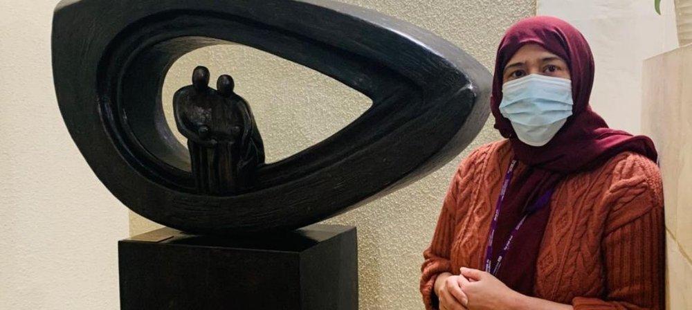 Romana standing next to statue