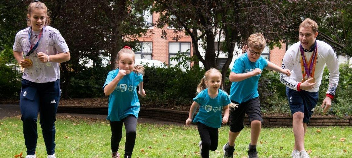 three GOSH patients run alongside two sporting heroes outside