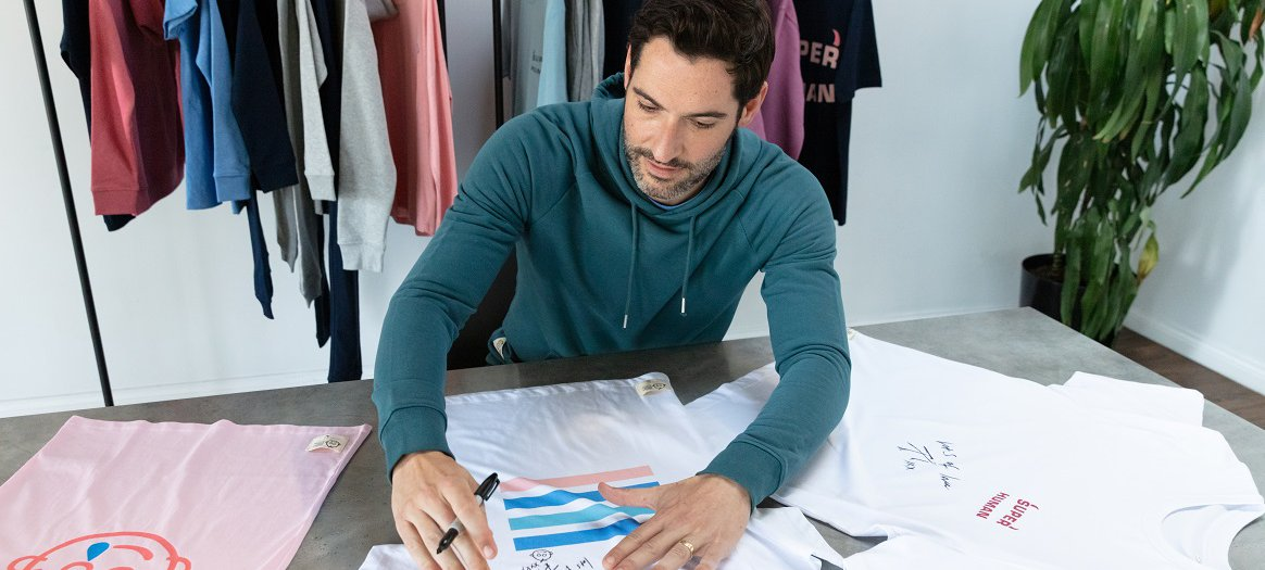 Tom Ellis signs a selection of clothes from the Rupert and Buckley collection