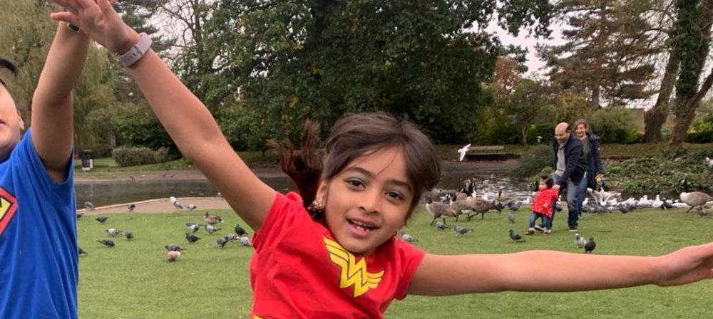 Aanya jumps in the air outside, smiling